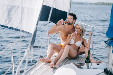 smiling couple in swimwear drinking champagne on yacht