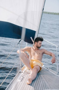 shirtless muscular man in swim trunks having sunbath on yacht