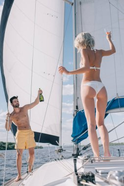 handsome shirtless man showing bottle of champagne to girlfriend with glasses on yacht