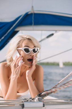 shocked young woman in sunglasses and swimwear talking on smartphone and laying on yacht