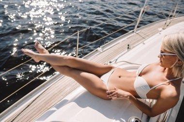 beautiful young woman in sunglasses and bikini having sunbath on yacht