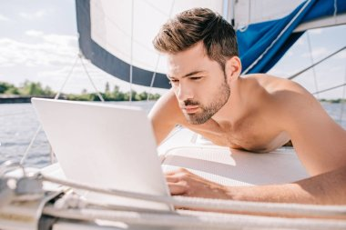 young shirtless man having sunbath and using laptop on yacht