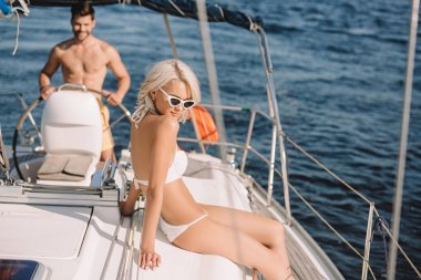 beautiful young woman in bikini having sunbath while her boyfriend steering yacht