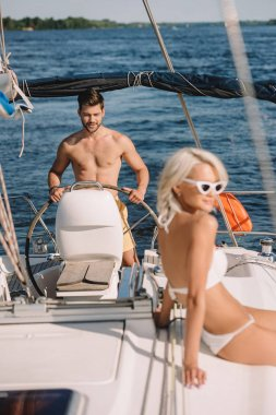 attractive young woman in bikini having sunbath while her boyfriend steering yacht