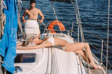 attractive young woman in bikini and sunglasses having sunbath while her boyfriend steering yacht