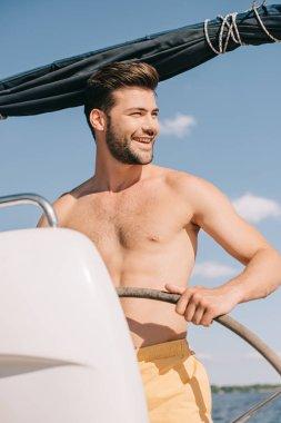 smiling shirtless muscular man in swim trunks steering yacht
