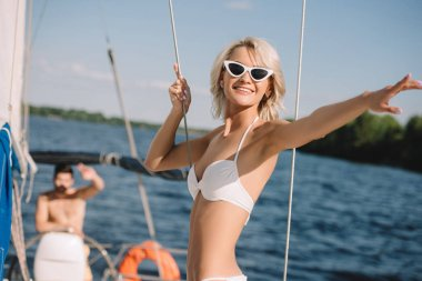 smiling woman in bikini and sunglasses pointing by finger to boyfriend standing behind on yacht
