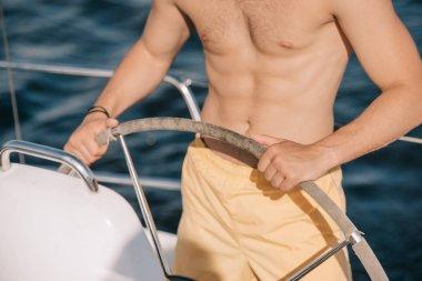 cropped image of shirtless muscular man in swim trunks steering yacht