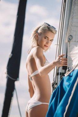 beautiful young woman in bikini looking at camera on yacht