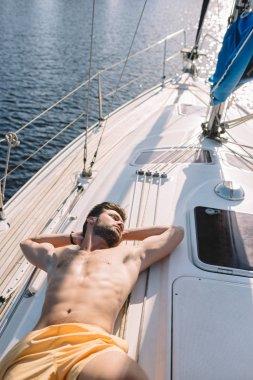 high angle view of shirtless muscular man in swim trunks having sunbath on yacht