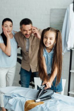 smiling daughter holding iron above burned shirt at home, parenthood concept