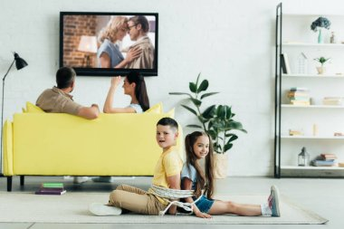 parents watching movie and children sitting tied with rope on floor at home