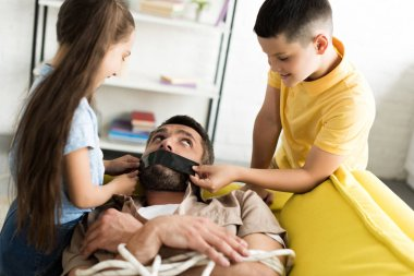 disobedient children closing father mouth with black tape at home, parenthood concept
