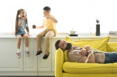 Fotografie children eating chocolate and father lying tied on sofa at home