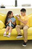 Fotografie sister and brother eating cream on sofa at home