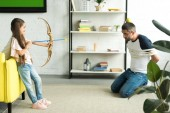 Fotografie side view of daughter playing with tied father and pretending shooting with toy bow at home