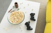 pohled z úhlu vysoké skleněné mísy s popcorn a joysticky na stole v obývacím pokoji