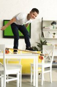 Fotografie pre-adolescent boy standing on skateboard on table at home and looking at camera