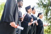 young graduated students in capes and hats holding rolled diplomas