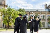 Fotografia young graduated students with diplomas greeting each other in college garden