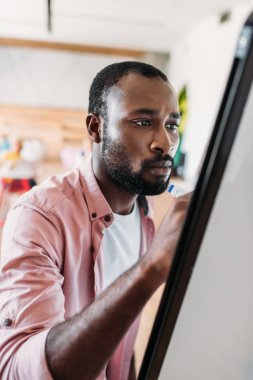 concentrated young african american man writing on whiteboard