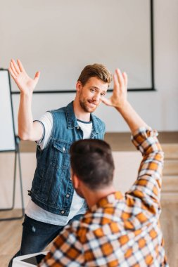 successful young students giving high five at college