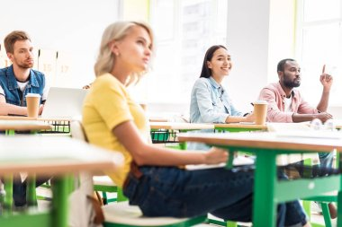 focused young students sitting in classroom during lesson