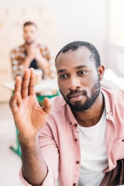 close-up portrait of young african american student raising hand to answer on teacher question