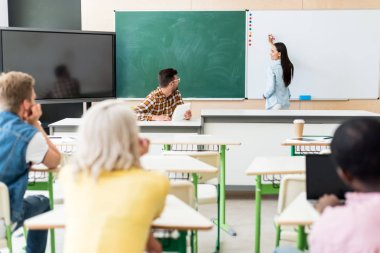 rear view of young students sitting in classroom during lesson