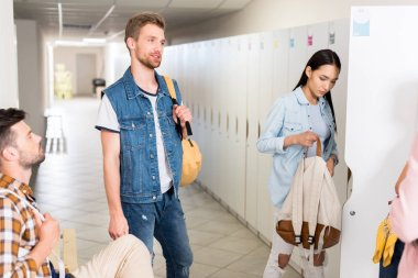 young students spending time together and chatting in college corridor