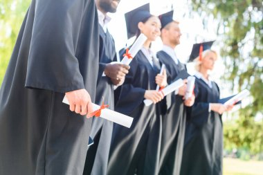 cropped shot of graduated students in capes and hats holding rolled diplomas