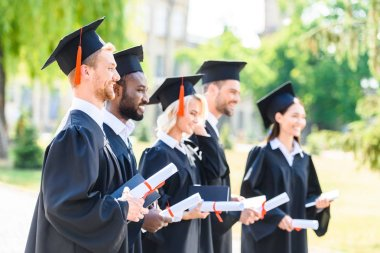 happy graduated students in capes and hats holding rolled diplomas