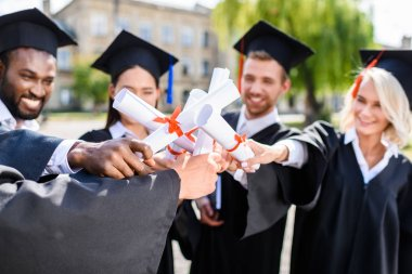 young graduated students making team gesture with rolled diplomas