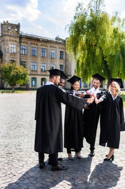 young happy graduated students making team gesture with rolled diplomas
