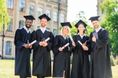 young graduated students in capes holding diplomas and looking at camera