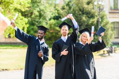 happy young graduated students in capes holding diplomas