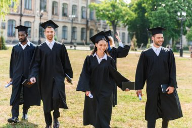 young graduated students in capes walking by university garden