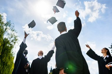 bottom view of young graduated students throwing up hats in front of blue sky
