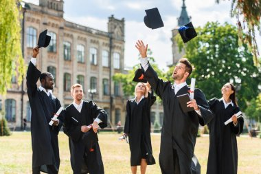 young happy graduated students throwing up graduation caps in university garden