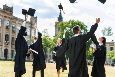 young graduated students throwing up graduation caps in university garden