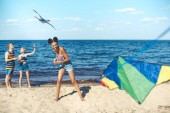 Selektivní fokus multikulturní přátel s draky společně trávit čas na písečné pláži
