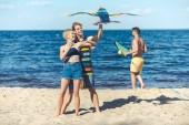 Skupina mladých přátel se draka spolu trávili čas na písečné pláži