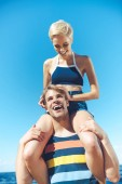 Photo low angle view of young woman sitting on boyfriends shoulders against clear blue sky