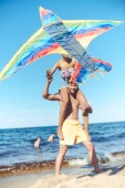 Fényképek selective focus of multiracial couple with colorful kite spending time on sandy beach