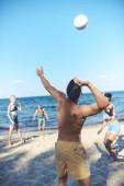 Fotografie Interracial přáteli, kteří hrají volejbal společně na písečné pláži