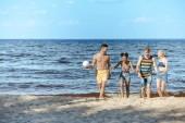 multikulturní přátelé s volejbalový míč na písečné pláži