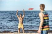 Selektivní fokus mladých mužů, které hraje s létající disk na písečné pláži