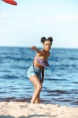 Photo african american woman throwing flying disc on sandy beach