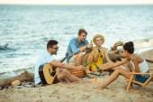 mnohonárodnostní usmívající se přátelé s nápoje a akustická kytara společně odpočívající na pláži
