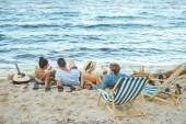 Hátulnézet a többnemzetiségű meg pihen a homokos strandon takaró